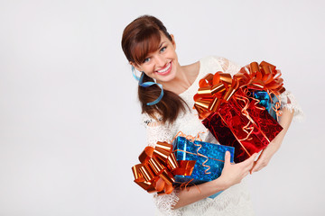 Smiling woman in white dress holds three red and blue boxes