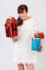 Pretty woman in white dress holds red and blue boxes with gifts.