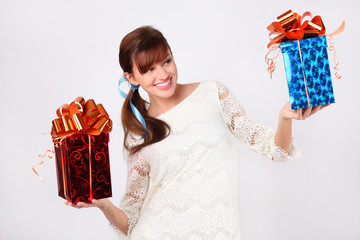 Pretty woman in white dress compares boxes with gift