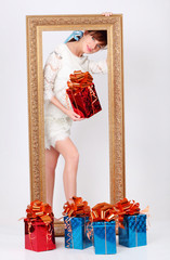 Girl with box with gift stands behind gilt frame standing