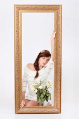Beautiful woman in white openwork dress sits on floor behind big