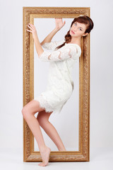 Beautiful young woman in white dress comes out of big gilt frame