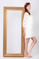 Beautiful young woman in white dress stands near big gilt frame