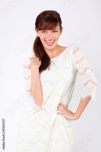 Beautiful young woman wearing in white openwork dress laughs.