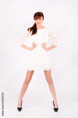 Beautiful young woman in white openwork dress holds by waist