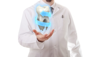 Male dentist showing a molar tooth