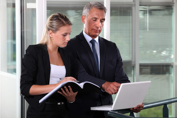 Businessman and young assistant rushing to prepare presentation