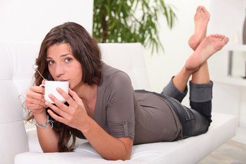 Woman drinking coffee on the sofa