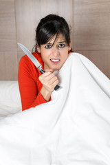 Scared woman with knife in bed