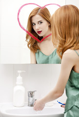 Redhead girl near mirror with heart it in bathroom.