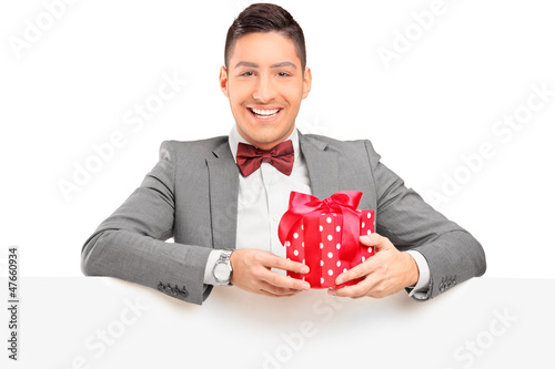 Handsome guy with bow tie holding a gift behind a panel