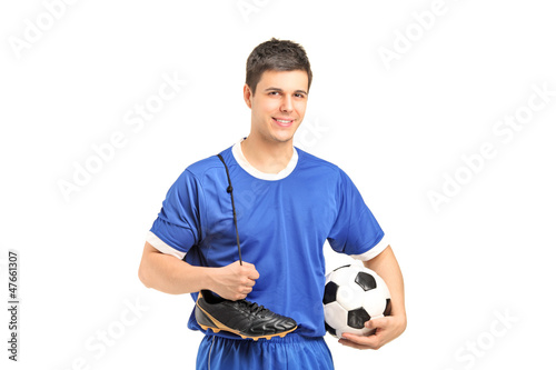 Smiling footballer in sport wear holding a soccer shoes and foot