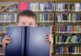 Boy with Blue Book in Library