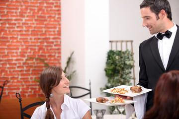 women at restaurant with waiter