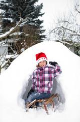 Kind spielt mit weihnachtsmütze im Schnee