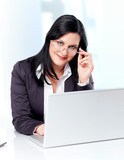 Competent business woman with laptop and a pair of glasses