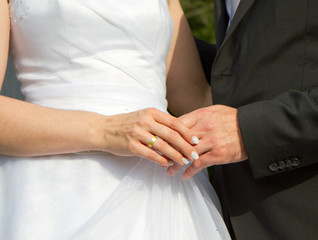 bride and groom holding hands after wedding show there rings