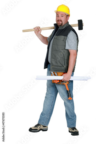 Laborer holding plans and sledge-hammer