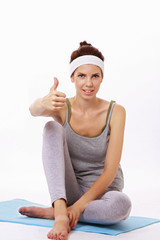 Young yoga girl showing thumb up isolated on white background