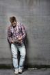 Jugendlicher ließt von einem Tabletpc an eine Wand angelehnt
