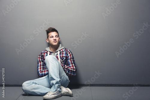 Jugendlicher sitzt angelehnt an eine Wand