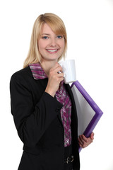 attractive female student holding mug of coffee and files