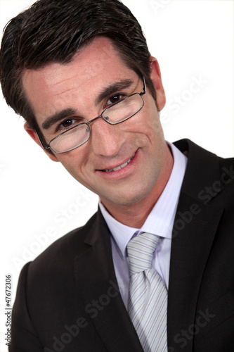 Portrait of a businessman peering over his glasses