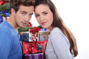 Young couple stood with pile of presents