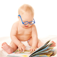 Baby in glasses reading a book and learning