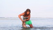 Beautiful woman holding her baby and playing in ocean