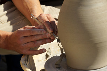 Potters hands creating a clay vase on a turning wheel