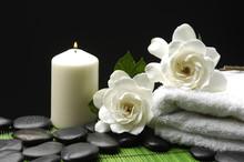 Gardénia blanc et pierres avec une serviette et bougie sur le tapis vert