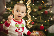 Infant Mixed Race Baby Enjoying Christmas Morning Near The Tree