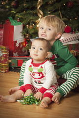 Mixed Race Baby and Young Boy Enjoying Christmas Morning Near Th