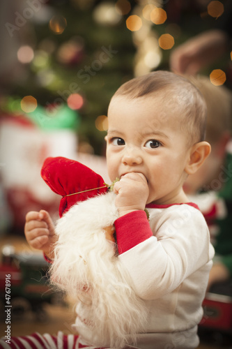 Infant Mixed Race Baby Enjoying Christmas Morning Near The Tree