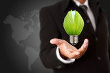 Businessman holding green light bulb