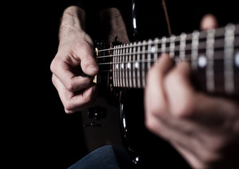 Human hand playing an electric guitar