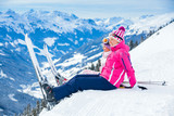 Young skier sitting on the hill