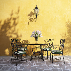 Romantic aged Italian village outdoor furniture on stucco wall