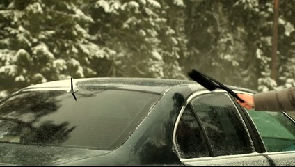 Man cleans the car out of the snow near highway