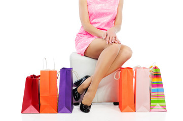Young woman with slim legs sitting near colorful shopping bags