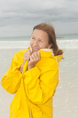 Woman raincoat autumn storm at beach