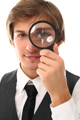 Smiling man in a suit looking through magnifier
