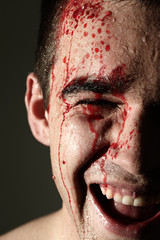 Close up of laughing man face in blood