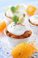 Cakes on a lace napkin decorated with easter eggs.