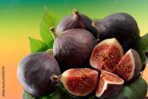 Several fresh figs with leaves, whole and cut