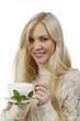 Hübsche Frau hält lächelnd eine Tasse Tee