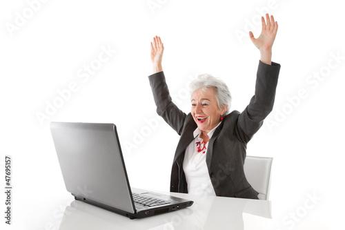 Ältere Frau mit PC ist happy