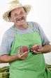 Biobauer hält frisch geerntete Pfirsiche in der Hand