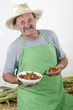 Biobauer mit einigen Kirschpaprika in der Hand